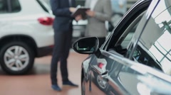 Blurred customer and seller behind a car Stock Footage