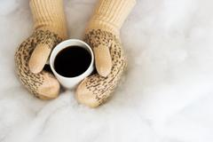 Woman hands in teal gloves are holding a mug with hot coffee or cocoa. - stock photo