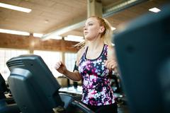 Young female running on treadmill in health club Stock Photos