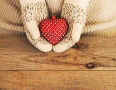 Woman hands in light teal knitted mittens are holding red heart on wooden bac - stock photo