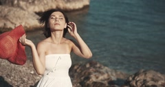 Stock Video Footage of the Asian girl in a white dress costs on the coast and smiles