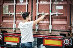 Stock Photo of Young Man with Large White Box by Freight Train