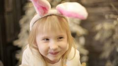 Baby girl in white costume of rabbit eats a carrot among christmas decorations. Stock Footage