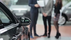 Blurred couple and seller behind a car Stock Footage