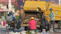 Stock Video Footage of Men loads refuse lorry with old offerings at shrine,Phnom Penh,Cambodia