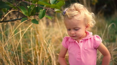 A cute little girl picks an apple off of the ground Stock Footage