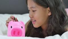 Happy Asian girl saving money in piggy bank Stock Footage