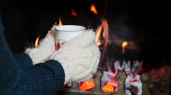 Keeping warm by the fireplace with a mug of hot tea. Stock Footage