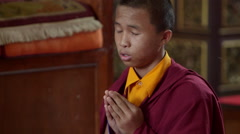 Young Tibetan buddhist monks chanting the puja ceremony in rural Nepal. - stock footage