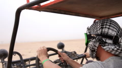 Guy and girl are racing buggy through the desert Stock Footage