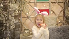 Baby girl in white costume of rabbit sits among christmas decorations. Stock Footage