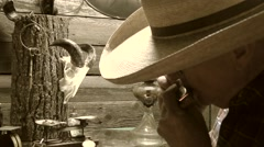 Sepia, Cowboy playing the harmonica in old cabin Stock Footage