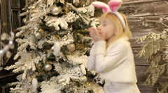 Small girl in white costume of rabbit decorates the Christmas tree. Stock Footage