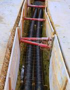 thick polyethylene pipes in the excavation of the road construction site for - stock photo