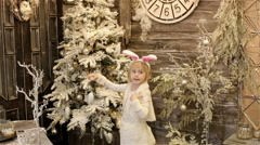 A small girl decorating a Christmas tree - stock footage