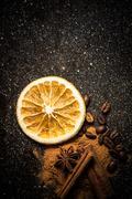 Star anise, cinnamon, coffe, orange and ground cinnamon on a black marble sla - stock photo