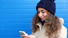 Girl with curly hair writing sms near blue wall with copy space Stock Footage