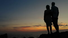 Couple standing on the cliff of a mountain holding hands and watching sunset Stock Footage