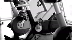 Black and white footage working out on the exercise bike in the gym Stock Footage