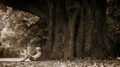 Stock Video Footage of Sepia footage of a boy sitting at the foot of a gigantic tree and reading