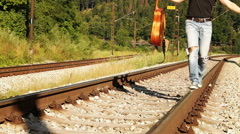 A male teenager walks balancing along the railway with the guitar - stock footage