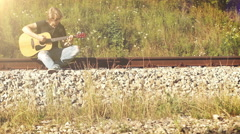 A long-haired guitarist sitting on the railway and playing Stock Footage