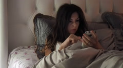 Woman Using Smart Phone in bed Stock Footage