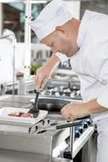 Chef prepares beef steak in pan at the kitchen Stock Photos