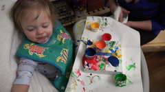 Mom helping baby finger paint art dripping paint on canvas creates smiles. - stock footage