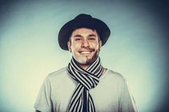 Stock Photo of Happy man with half shaved face beard hair in hat.