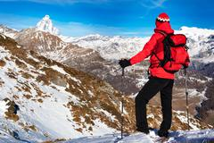 Hiker takes a rest admiring the Matterhorn peak. - stock photo