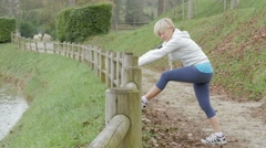 Senior woman stretching after exercising in natural landscape - stock footage