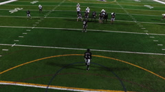 A football player punts the ball during a game, view from above - stock footage