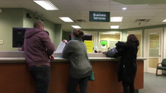 People at business service counter talking to the teller inside TD Bank - stock footage