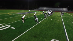 The camera pans overhead as a football player avoids being tackled and makes a Stock Footage