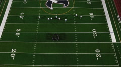 Football players line up at the line of scrimmage, birds eye view from high up Stock Footage