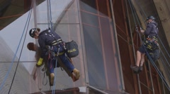 Stock Video Footage of Sydney Opera House window cleaners abseil, clean glass facade