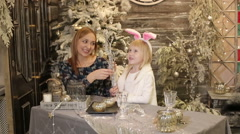 Mother and daughter in white costume of rabbit near the Christmas tree. Stock Footage