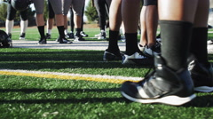 Football players standing around before a game, close up on the cleats Stock Footage