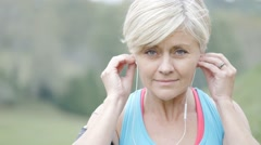 Senior woman exercising with earphones on - stock footage