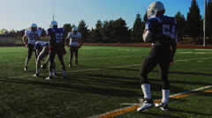 A football player gets tackled during a scrimmage game - stock footage