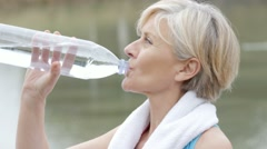 Senior woman drinking water after exercising - stock footage