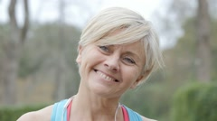 Portrait of senior woman in fitness outfit and earphones on Stock Footage