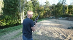 Man Firing weapon at outdoor target practice  Stock Footage
