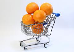 small shopping cart with many clementines - stock photo