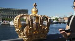Woman passes Crown on Bridge Stockholm in Summer sunshine - stock footage