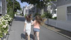 Two Teen Girls Hold Hands And Skip Down Historic New England Neighborhood Street - stock footage