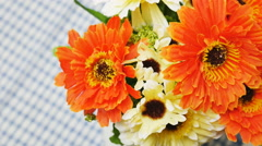 Orange artificial flowers on the dining table - stock footage