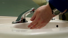 Man washing hands in a public washroom - stock footage