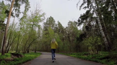 Woman runs on the forest road. Slow motion Stock Footage